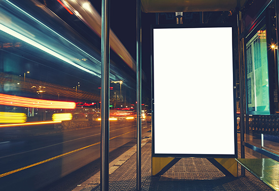 56580239 - illuminated blank billboard with copy space for your text message or content, advertising mock up banner of bus station, public information board with blurred vehicles in high speed in night city
